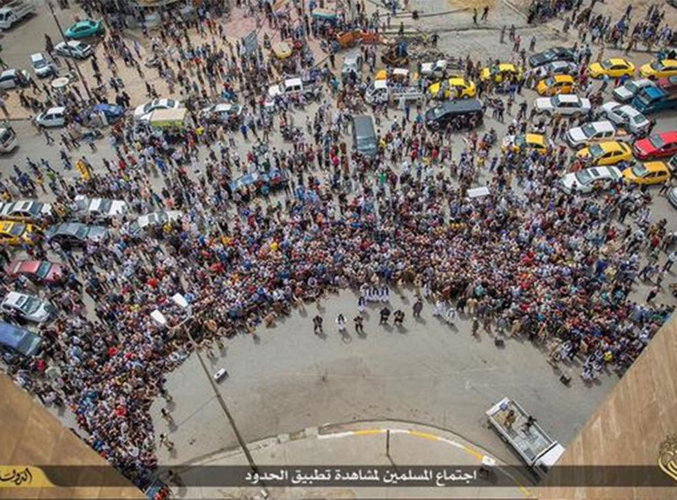 Bystanders gather as Isis militants throw a man suspected of being gay to his death