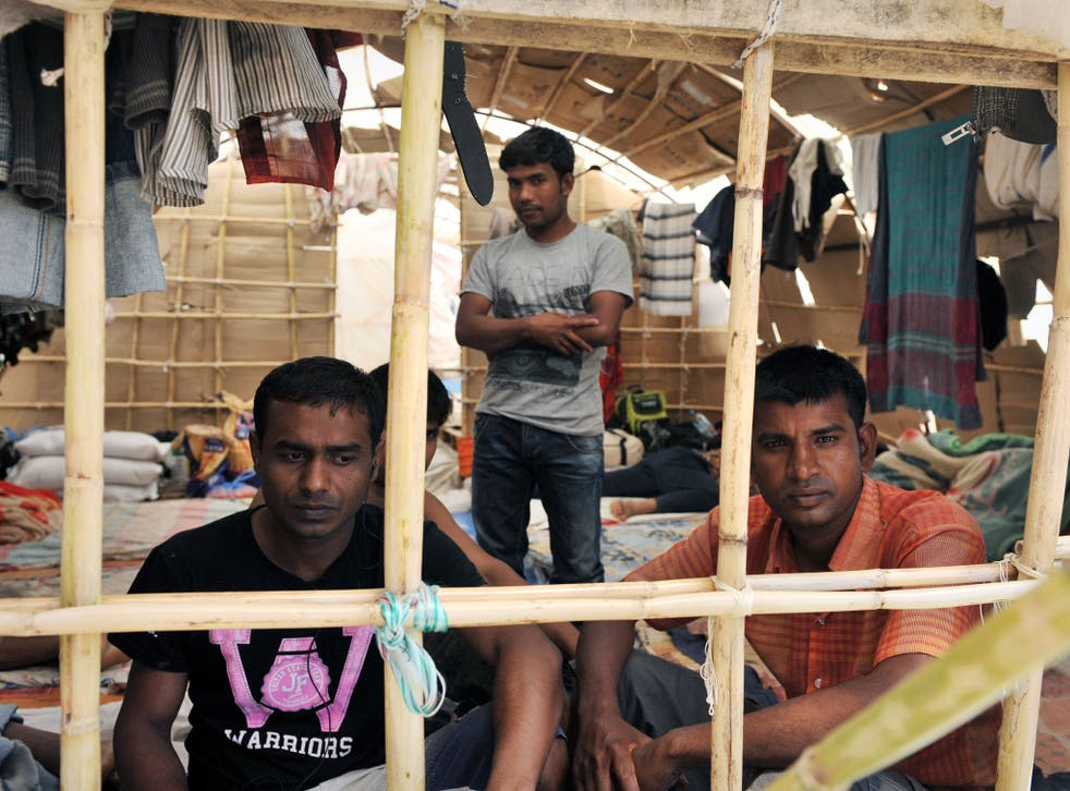 Migrant workers sit inside a makeshift camp in Manolada, circa 2013.