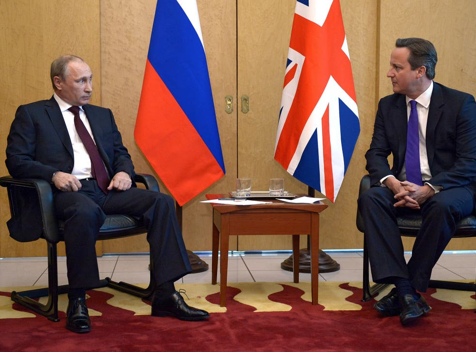 Russia's President Vladimir Putin (L) speaks with Britain's Prime Minister David Cameron (R) as they meet at Charles De Gaulle Airport in Paris on June 5, 2014