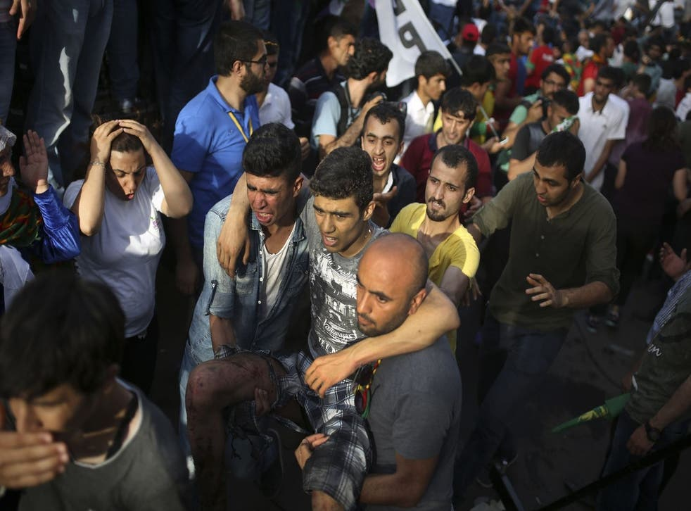 A youth is helped after being wounded in an explosion at a pro-Kurdish Peopleís Democratic Party (DHP) rally in Diyarbakir, southeastern Turkey, Friday, June 5, 2015 ahead of the general election on June 7, 2015. Two blasts occurred five minutes apart at