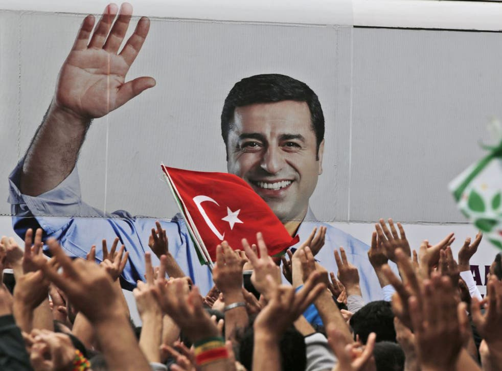 A bus carrying Selahattin Demirtas, his image on its side, drives off after a rally in Istanbul