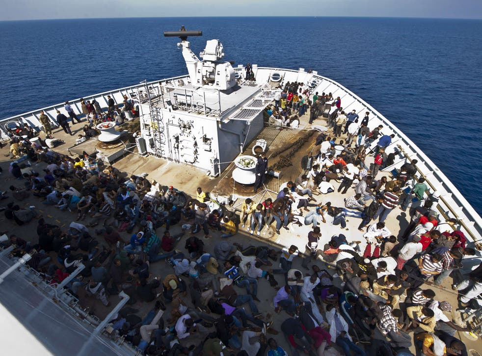 The rescued migrants sit on the deck of HMS 'Bulwark'