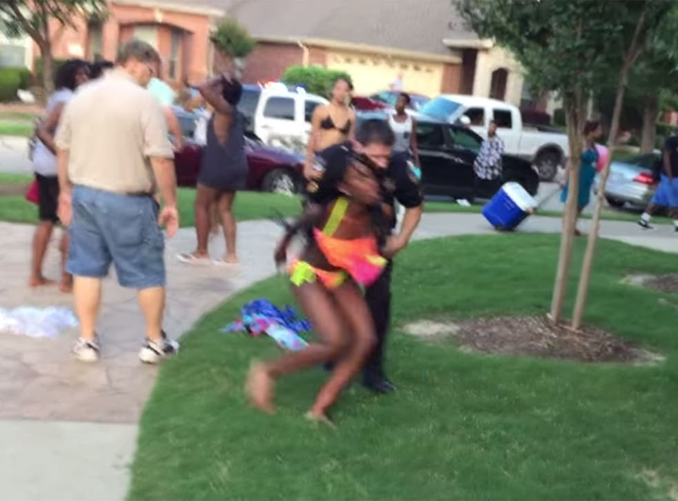 A Texas police officer has been placed on leave after video emerged of him throwing a 14-year-old African American girl to the ground, kneeling on her back and pointing his gun at teenagers who protested at her treatment