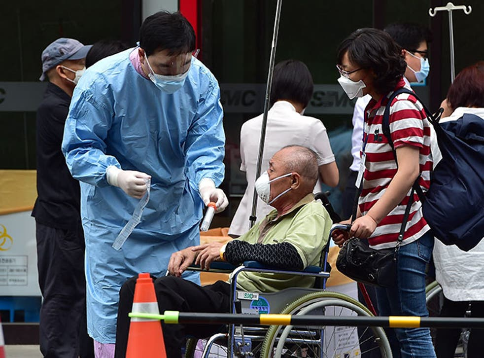 A medical worker from South Korea handles a sample tube from a man suspected of carrying the MERS virus