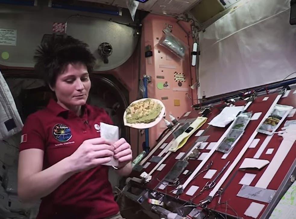 ESA astronaut, Samantha Cristoforetti prepares a meal on ISS