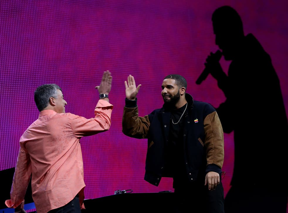 Apple's senior vice president of Internet Software and Services Eddy Cue (L) high fives with recording artist Drake during the Apple Music introduction at the Apple WWDC on June 8, 2015 in San Francisco, California