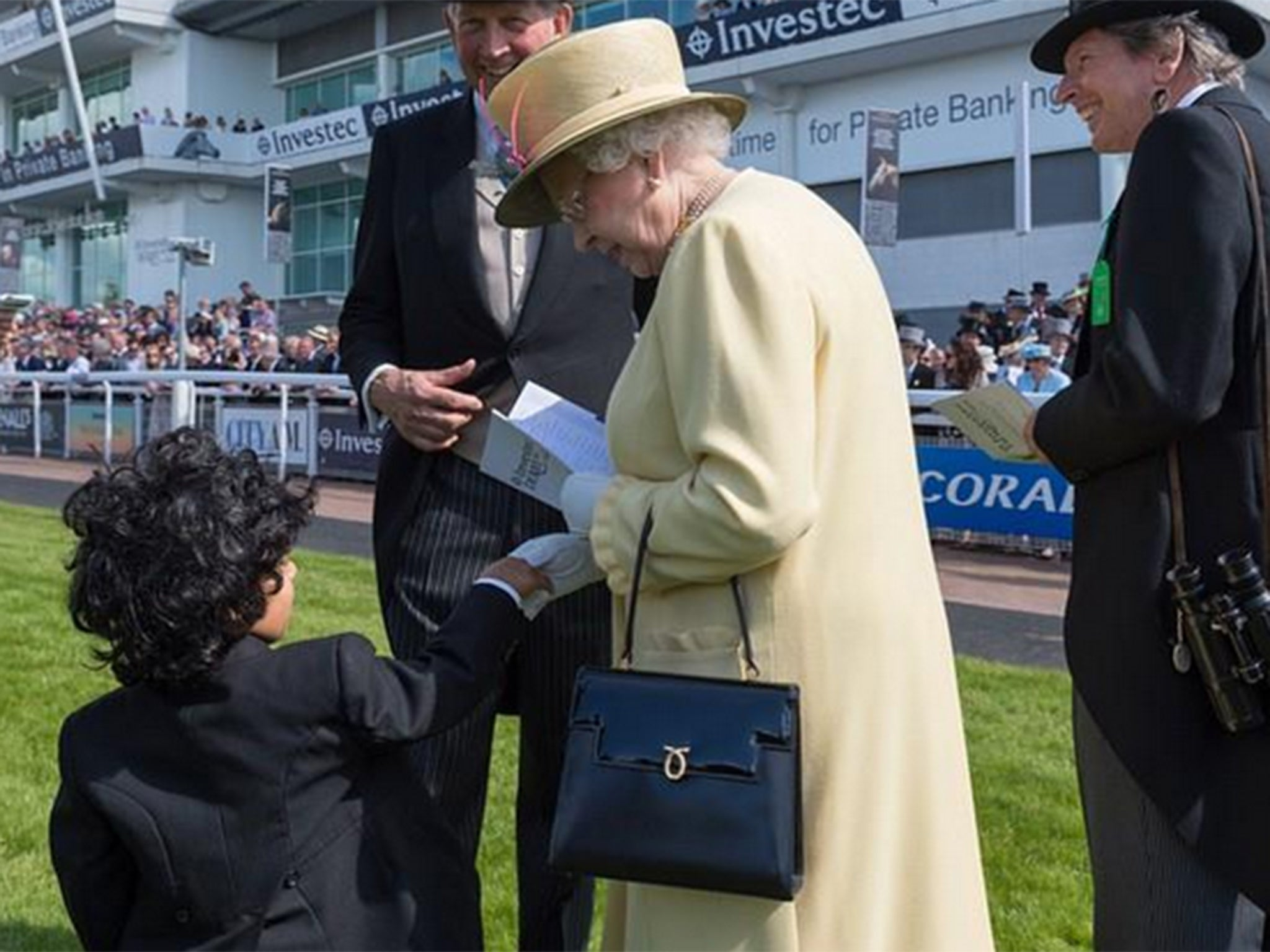 Young boy masters Royal etiquette by taking off his top hat to shake the Queen's hand