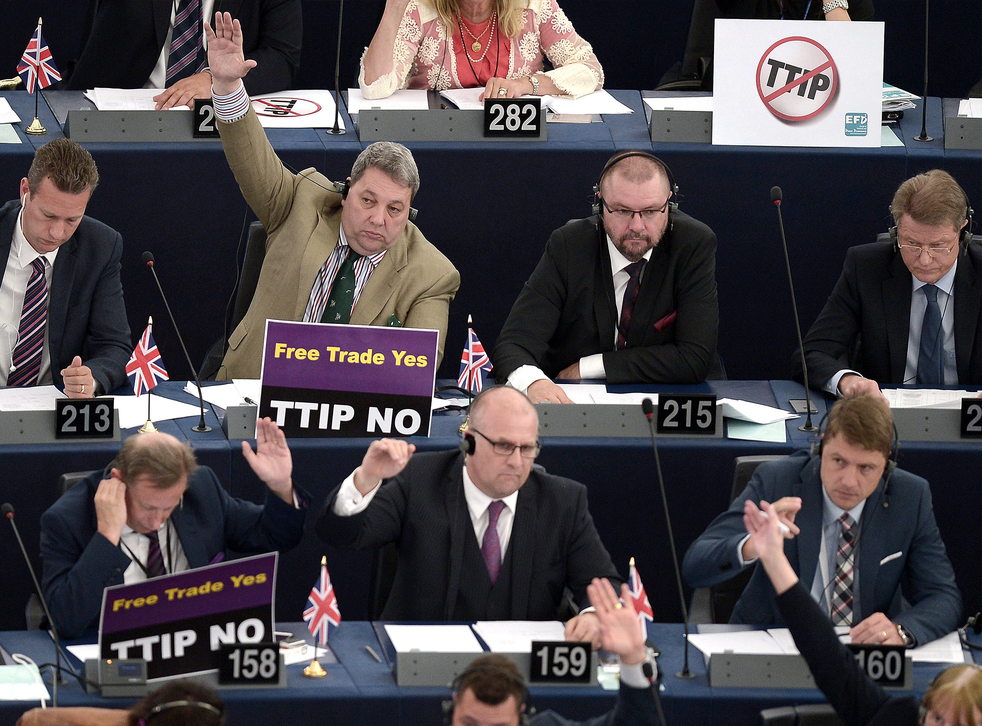 Members of the European Parliament take part in a voting session as they hold signs against TTIP