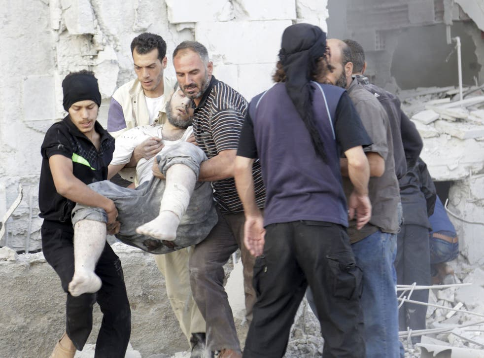 Residents carry an injured man at a site damaged by what activists said was a barrel bomb dropped by forces loyal to Syria's president Bashar Al-Assad in Maarat Al-Nouman, south of Idlib