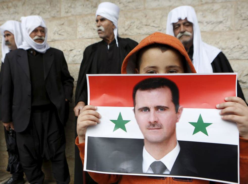 A boy from the Druze community, threatened by militants, holding a Syrian flag with the image of Bashar al-Assad during a rally marking Independence Day in a village on the Golan Heights