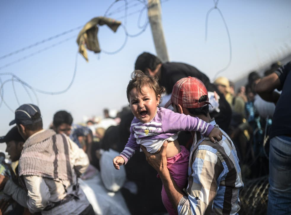 A Turkish man carries his child across the border (Photo: BULENT KILIC/AFP/Getty Images)