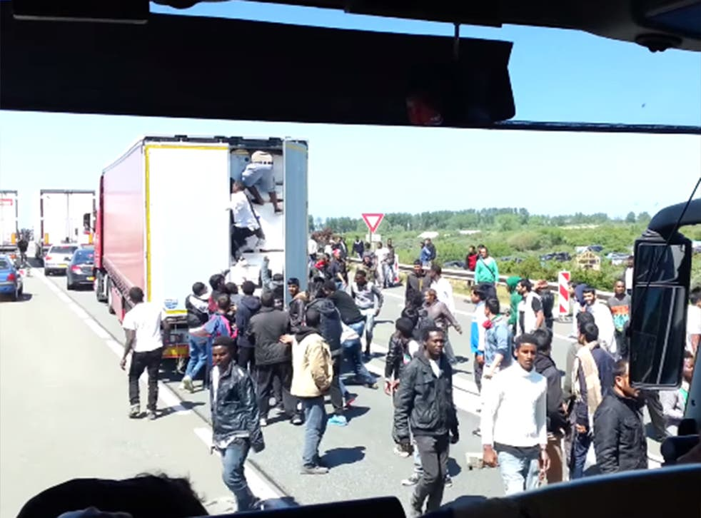 Migrants board a lorry leaving Calais