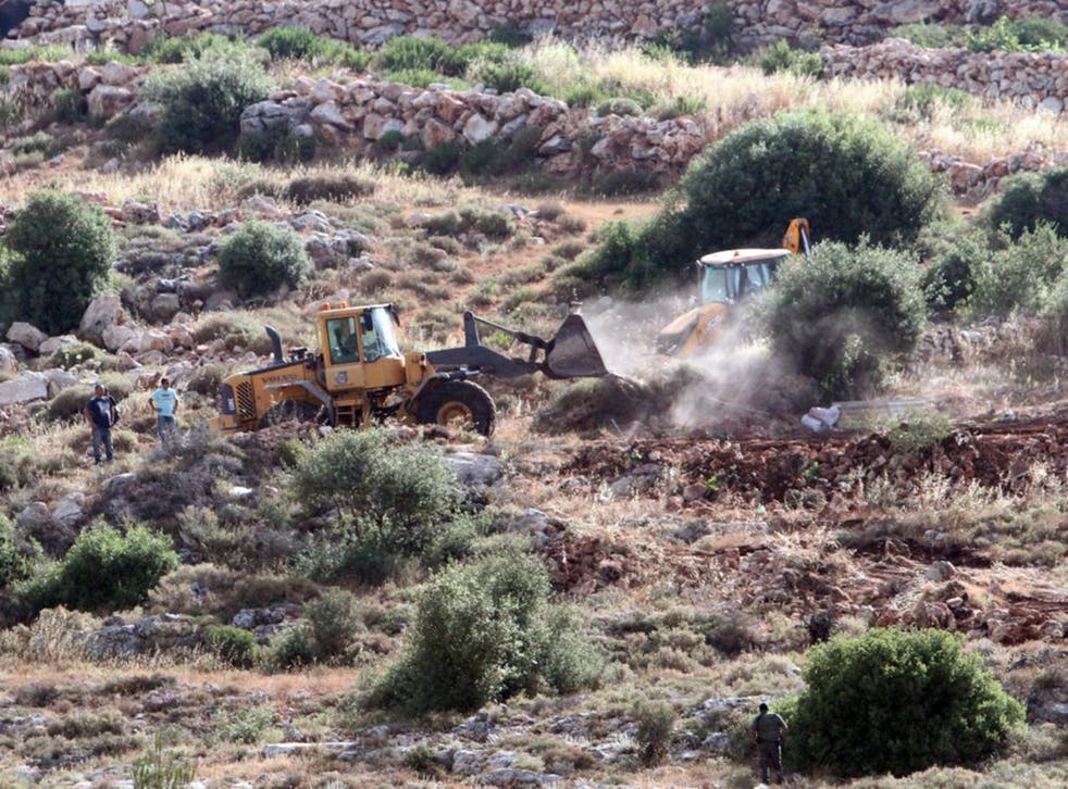 Bulldozers clear land for a new settlement in the West Bank village of Wadi Fukin last week