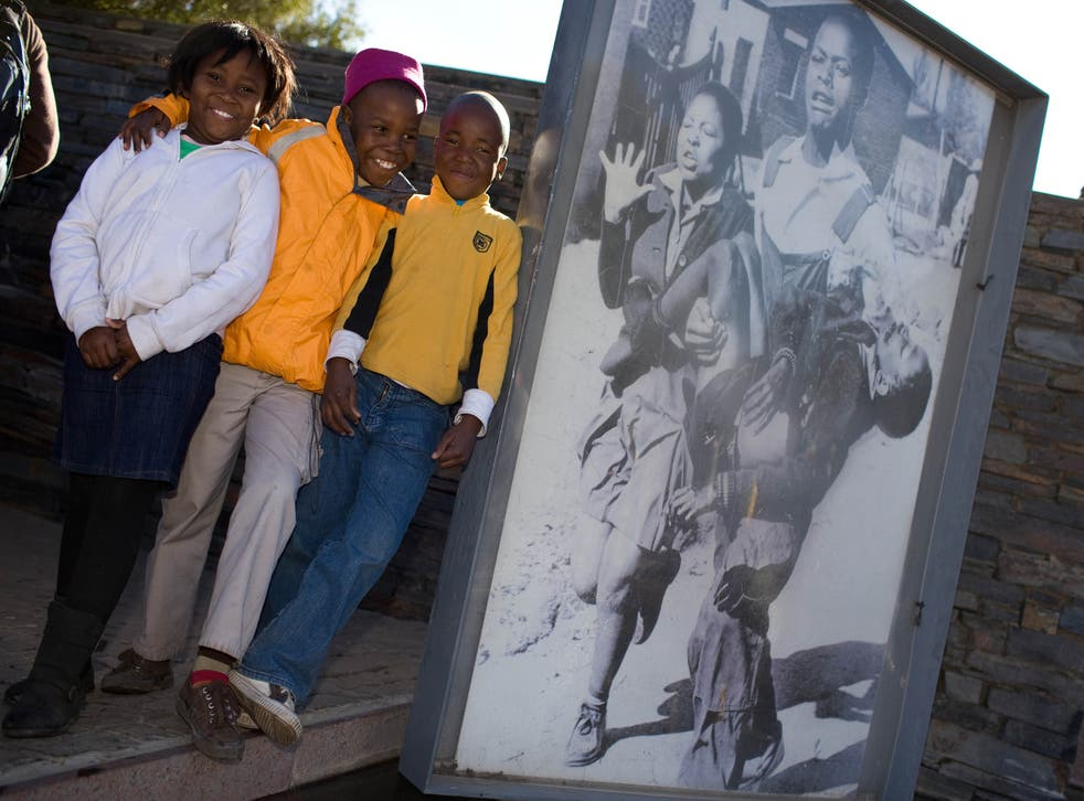 South African children pose next to the famous photo of 13-year-old Hector Pieterson being carried by students at Hector Pieterson Museum in Soweto on June 16, 2010.
