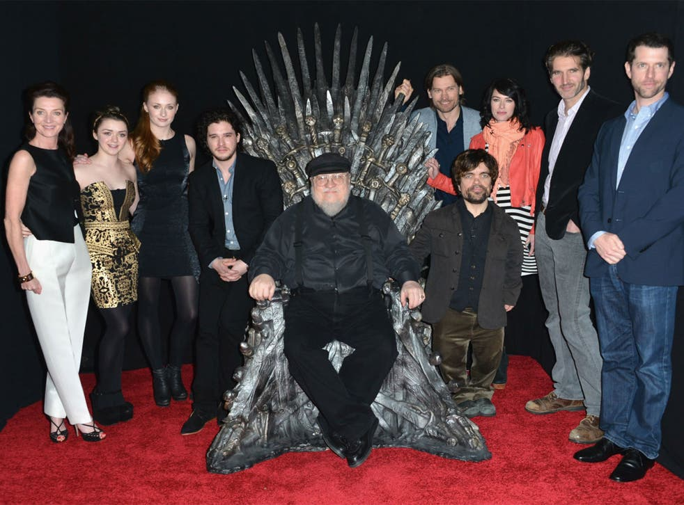 George RR Martin on the Iron Throne surrounded by past and present members of the Game of Thrones cast