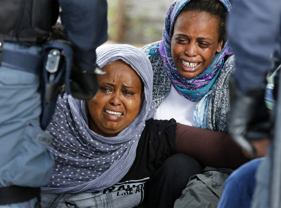 African migrants cry as Italian police stop them from crossing the border into France in Ventimiglia, Italy