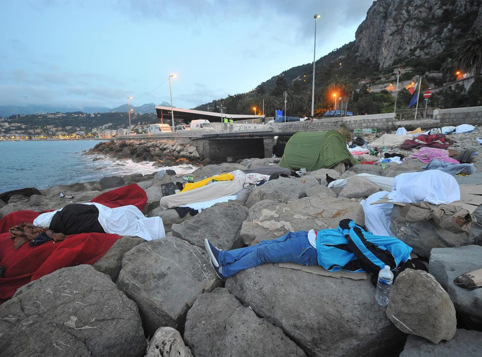Migrants sleep by the sea yesterday in Ventimiglia, Italy, near the French border, which they have been barred from crossing