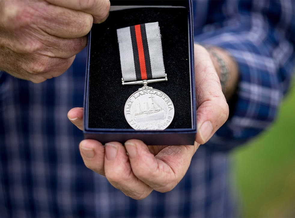 Tony Buss, 75, holds his father's 'HMT Lancastria' medal