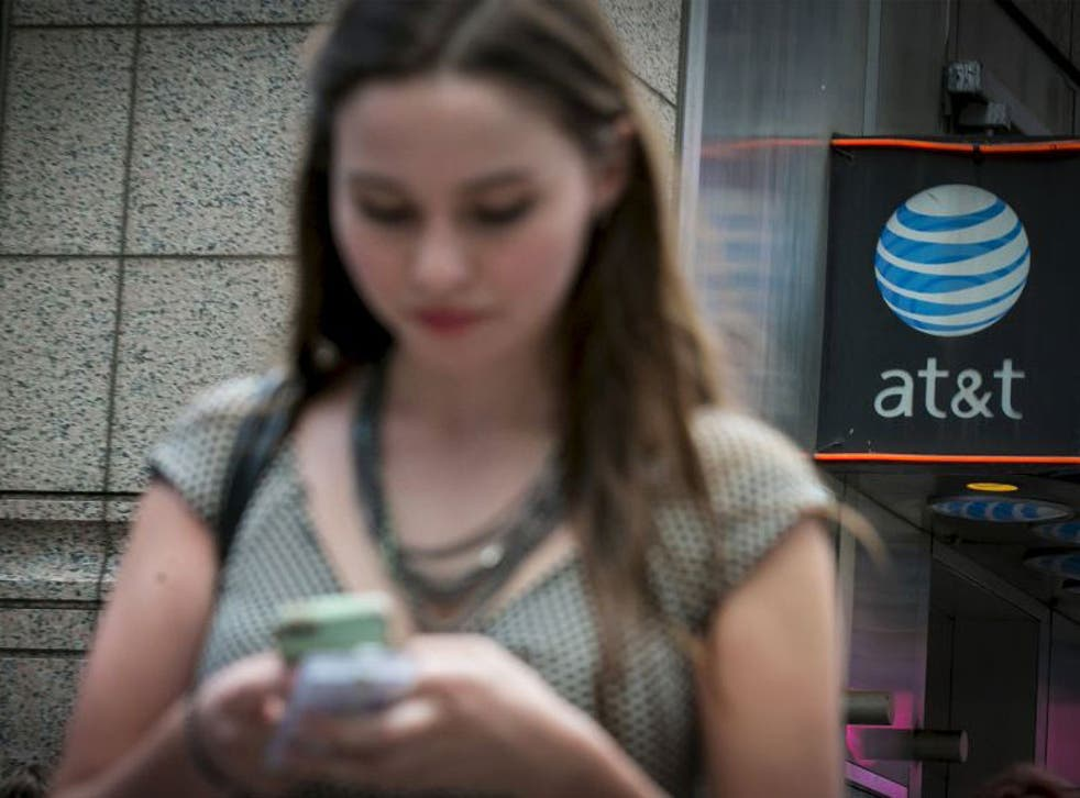 A woman uses her phone outside the AT&T store in New York's Times Square, June 17, 2015. The U.S. Federal Communications Commission on Wednesday proposed a $100 million fine for AT&T Inc, accusing the No. 2 wireless carrier of misleading customers who pai