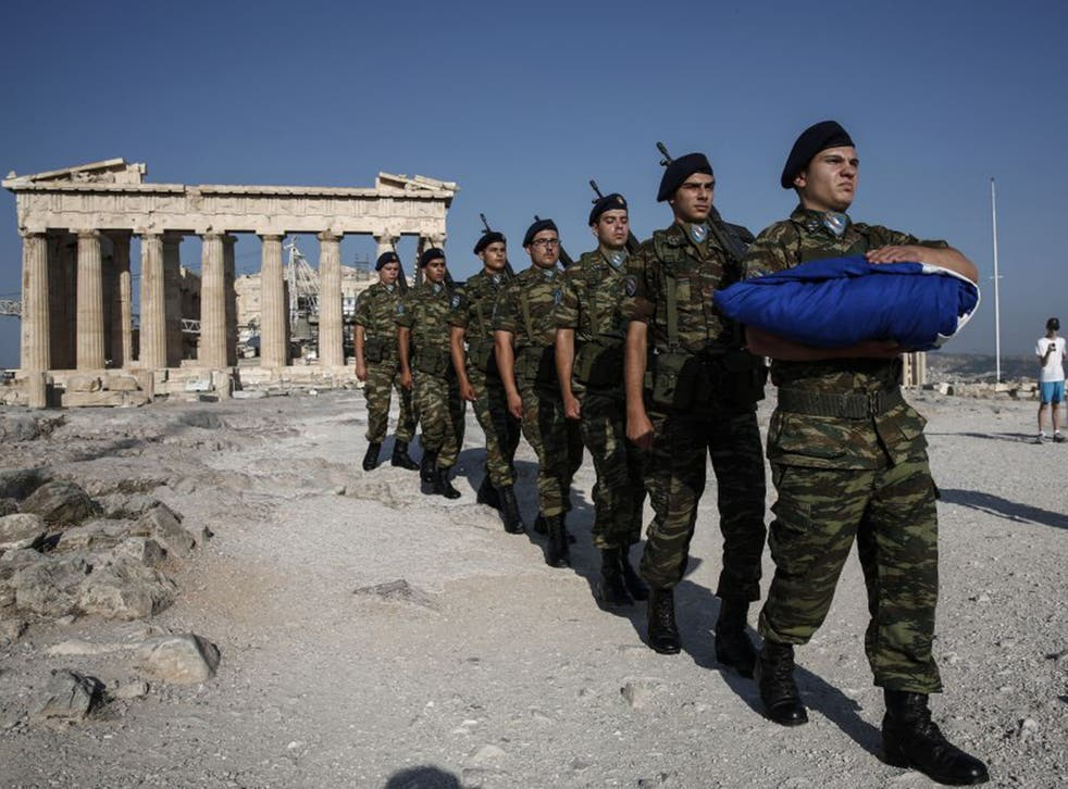 Soldiers carry the Greek flag to be hoisted at the Parthenon yesterday as the country lives through major uncertainty over its future