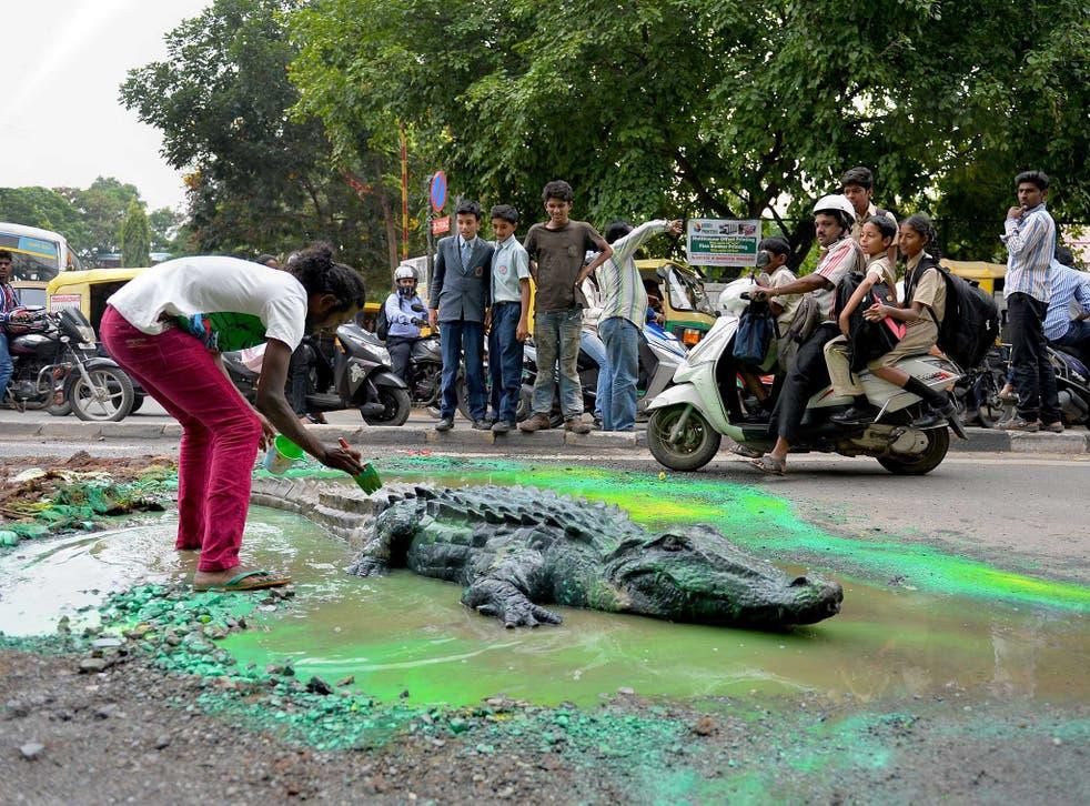Baadal Nanjundaswamy works on his crocodile