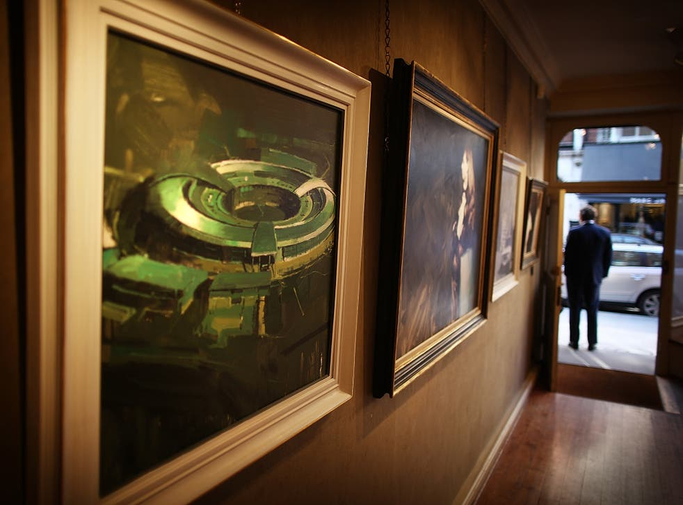 A painting of the government listening station GCHQ (L) is displayed at the 'A Year with MI6' exhibition at the Mount Street Gallery on February 14, 2011 in London, England