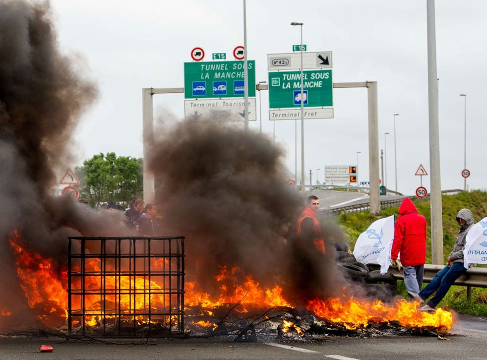 Striking employees of the French company My Ferry Link, a cross-channel ferry service, stand in front of tyres set on fire as they block the access to the Channel Tunnel in Calais, northern France