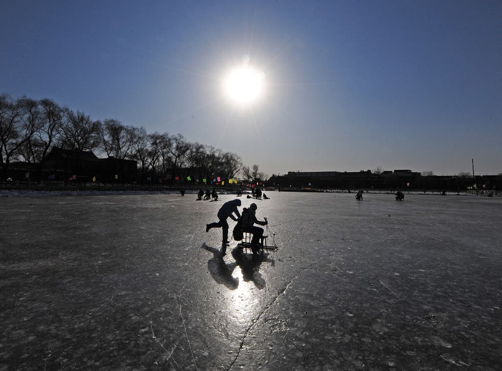 People play on a frozen lake at in central Beijing. File photo