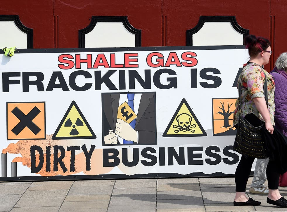 People walk past an anti-fracking banner as demonstrators outside Lancashire County Hall in Preston, protest against the applications from energy firm Cuadrilla to start two fracking operations on nearby sites