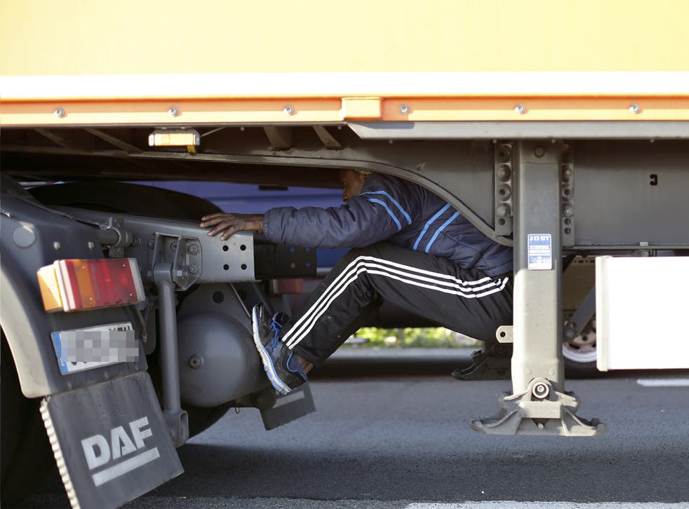 A migrant sits under the trailer of a lorry