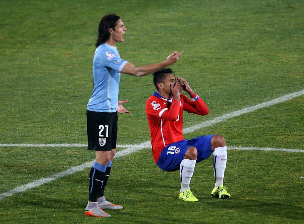 Gonzalo Jara falls down after clashing with Edinson Cavani