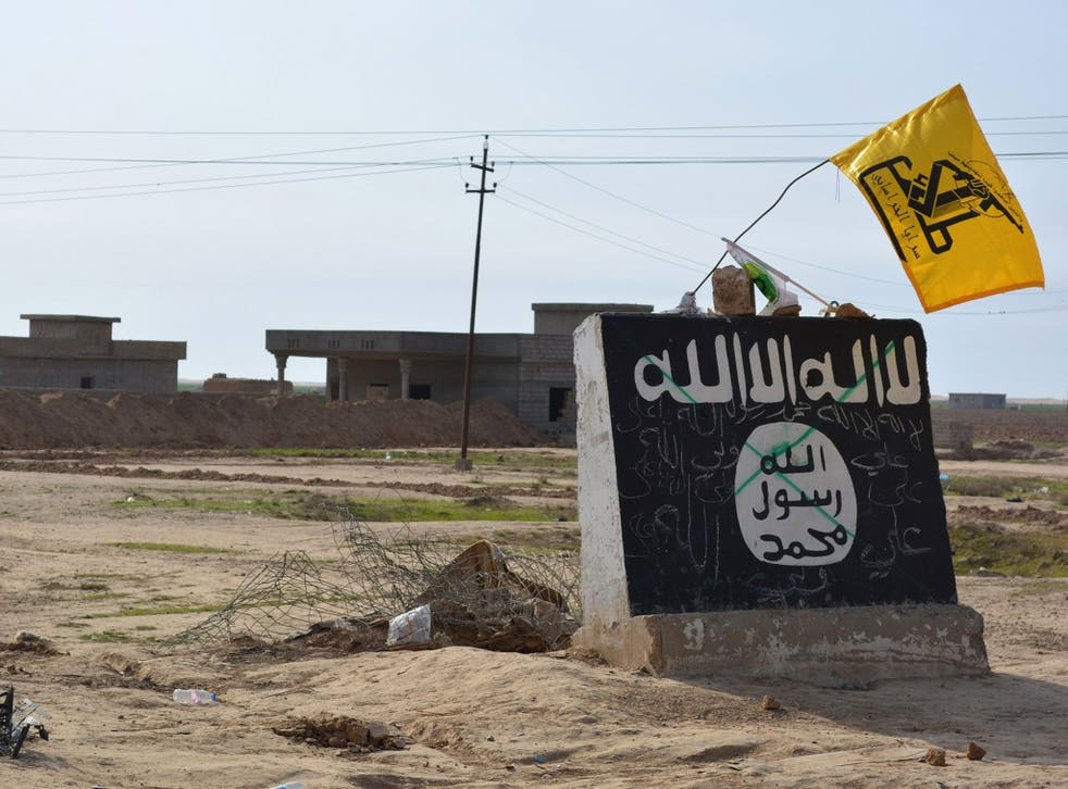A flag of the Shiite Hezbollah militant group flies over an Isis mural