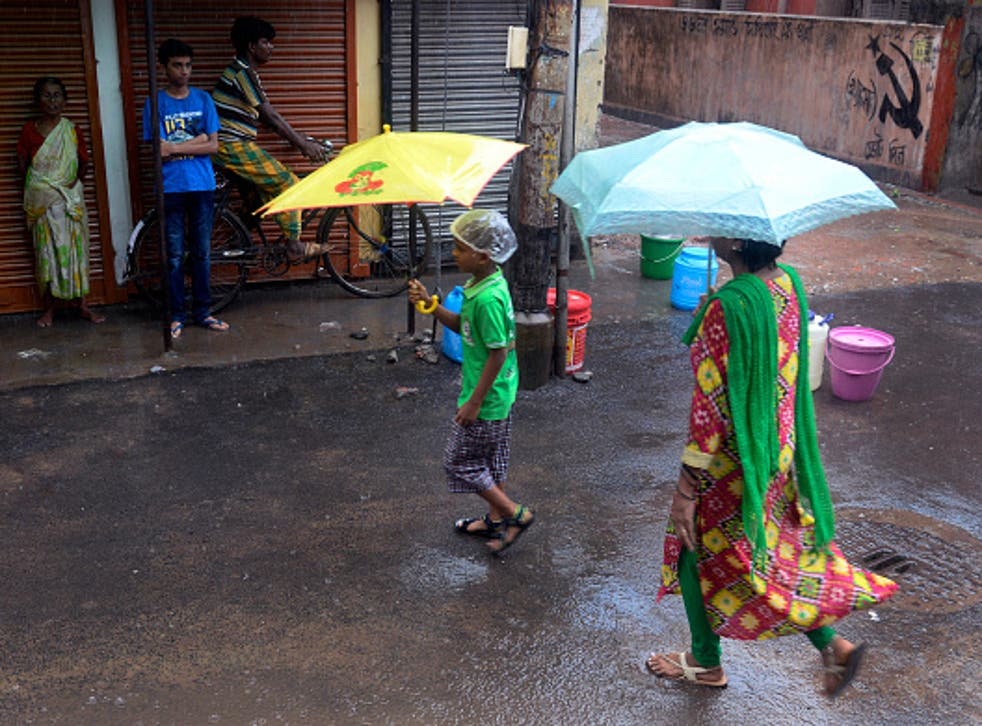 People in Kolkata shelter from the rain as the monsoon arrives