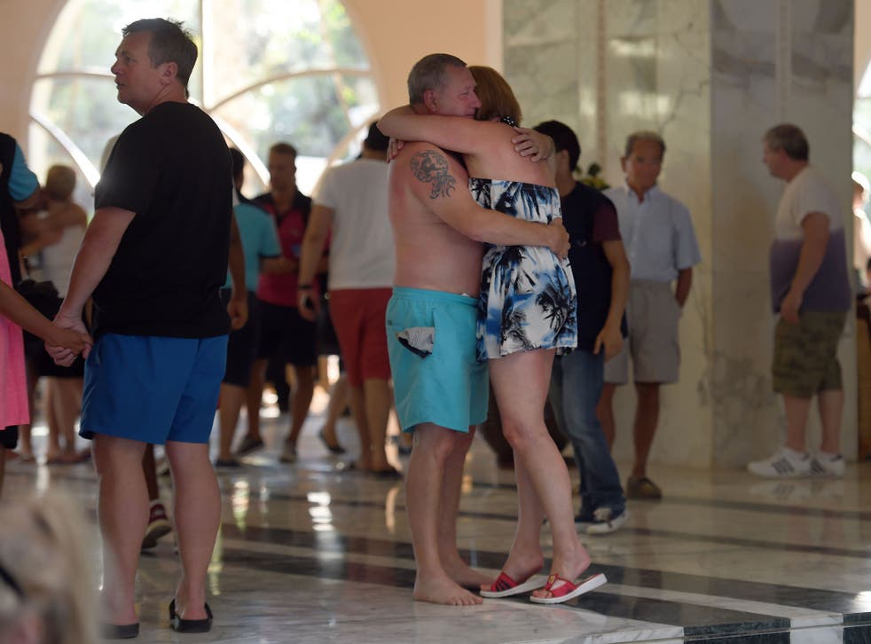Tourists comfort each other after the mass shooting in the resort town of Sousse