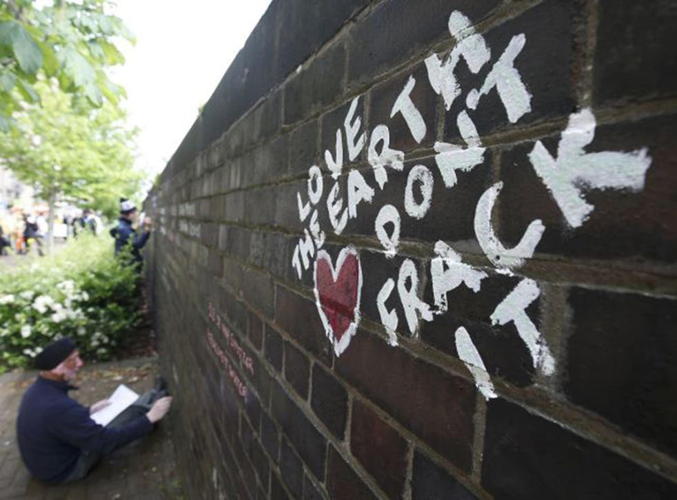 Anti-fracking protesters write messages on a wall during a demonstration outside County Hall in Preston last year