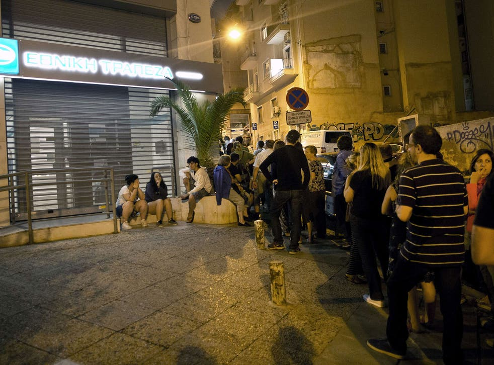 Greek people queue in front of an ATM mache to withdraw cash from a National Bank of Greece in central Athens on June 28, 2015