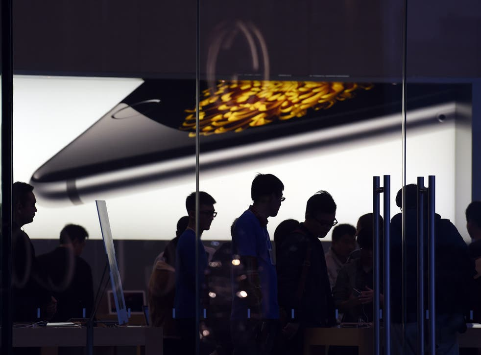 Store attendants help customers at an Apple store selling the iPhone 6 in Beijing on October 23, 2014