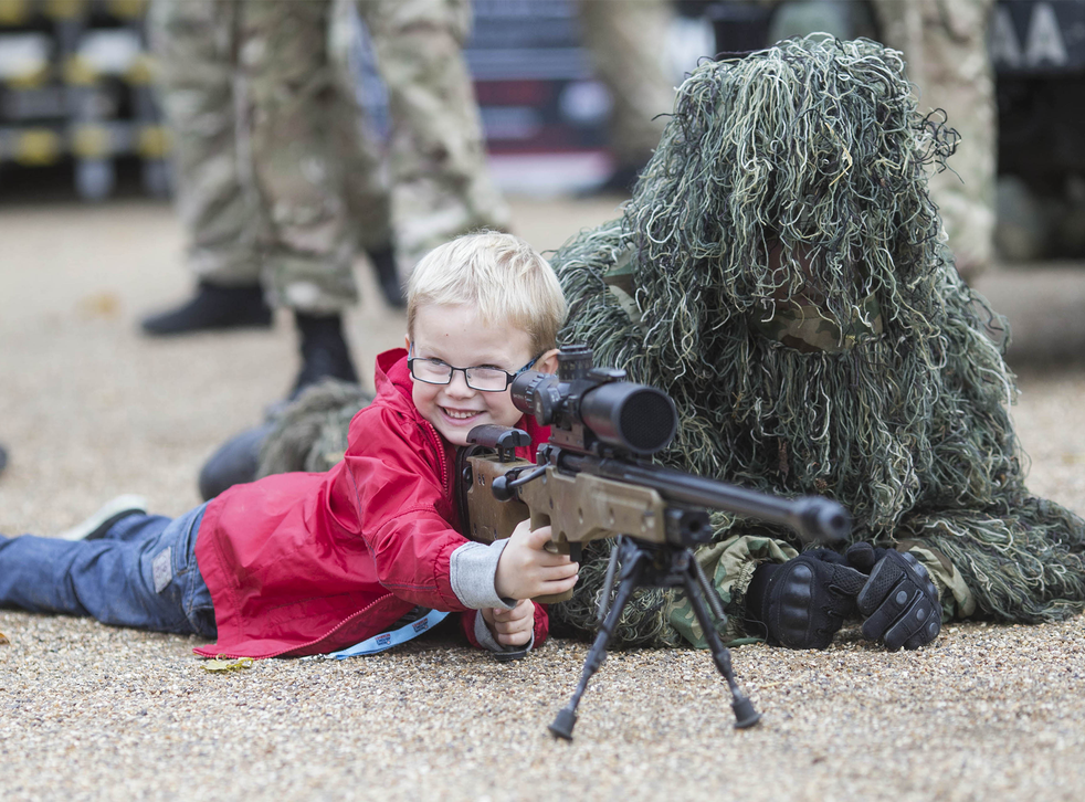 A 6-year-old boy has instruction at sniper shooting from a soldier at a Navy and Airforce recruitment fair in 2013
