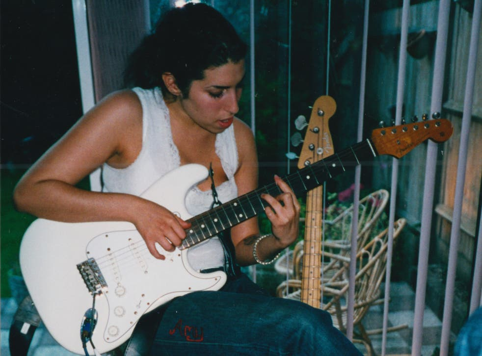 Amy Winehouse as a young girl, playing the guitar at her North London home