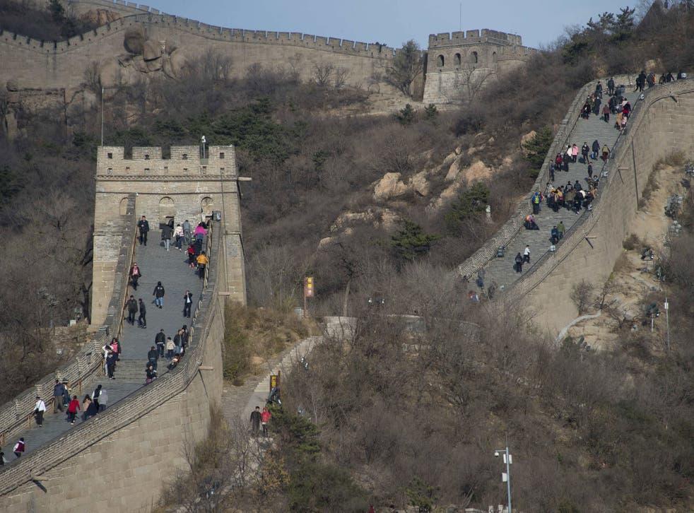 People walk along a section of the Great Wall of China at Badaling, north of Beijing, on November 11, 2014. AFP PHOTO/Nicholas KAMM