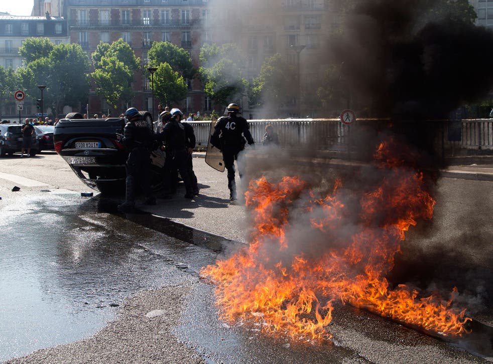 Riot police officers stand by an overthrown car during a taxi drivers demonstration in Paris, France. French authorities took two Uber managers into custody for questioning over 'illicit activity' involving its low-cost service. The detentions came amid r