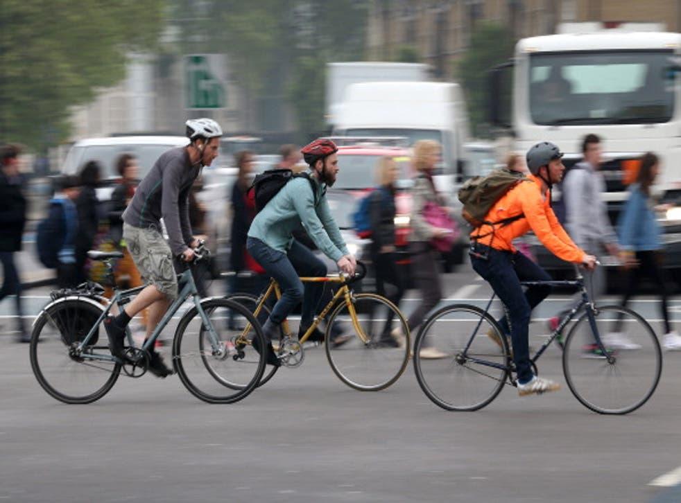 Cyclists cross a road junction near Vauxhall Bridge