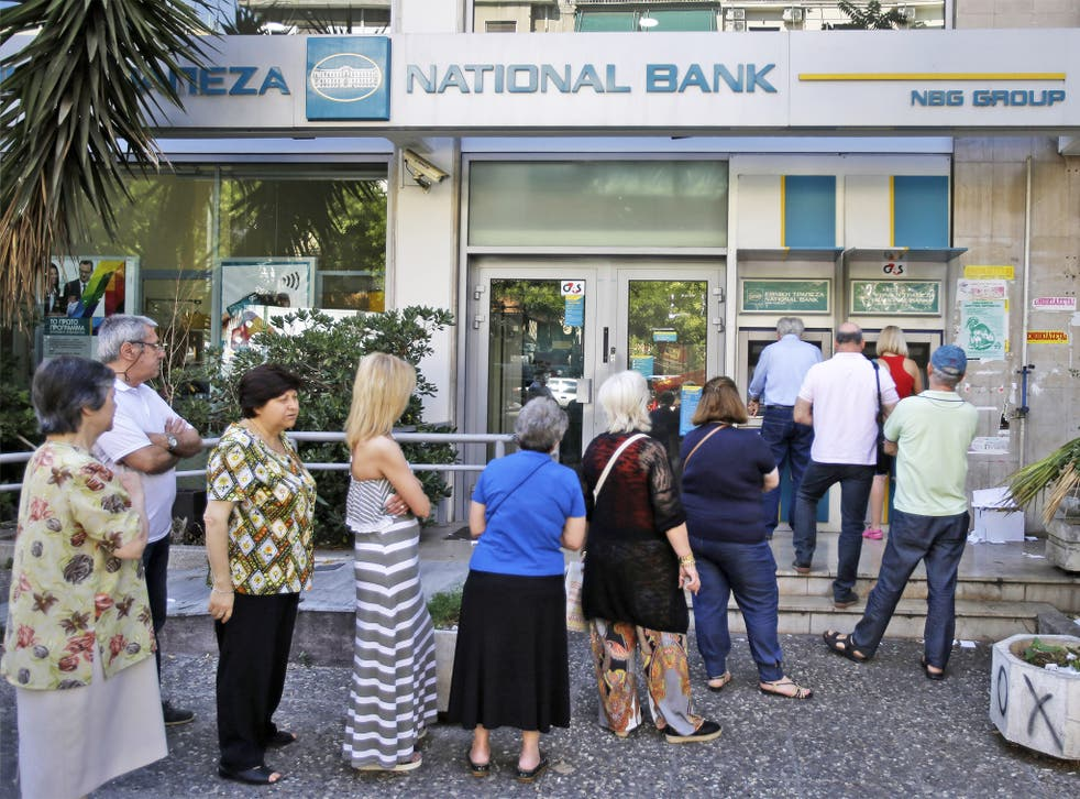 People stand in a queue to use an ATM outside a closed bank in Athens