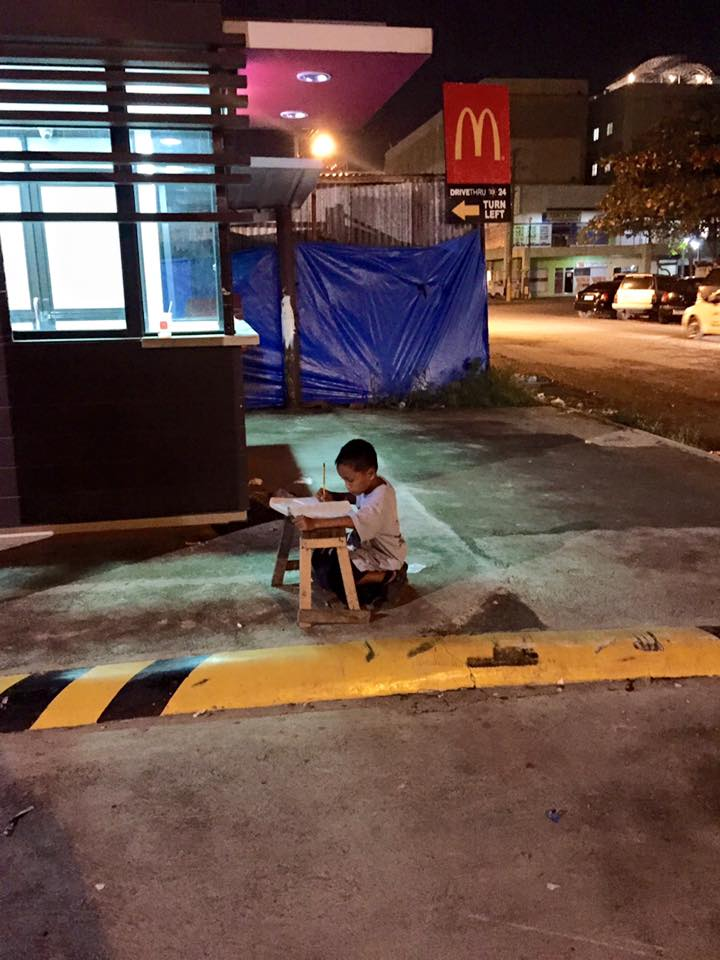 Poor homeless boy pictured doing his homework by McDonald's light after losing home in fire
