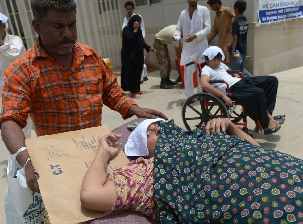 Pakistani relatives care for a heatstroke victim at a hospital in Karachi on June 30, 2015