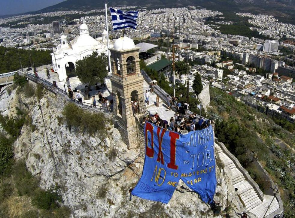 Anti-EU protesters hang a banner from Lycabettus hill in Athens