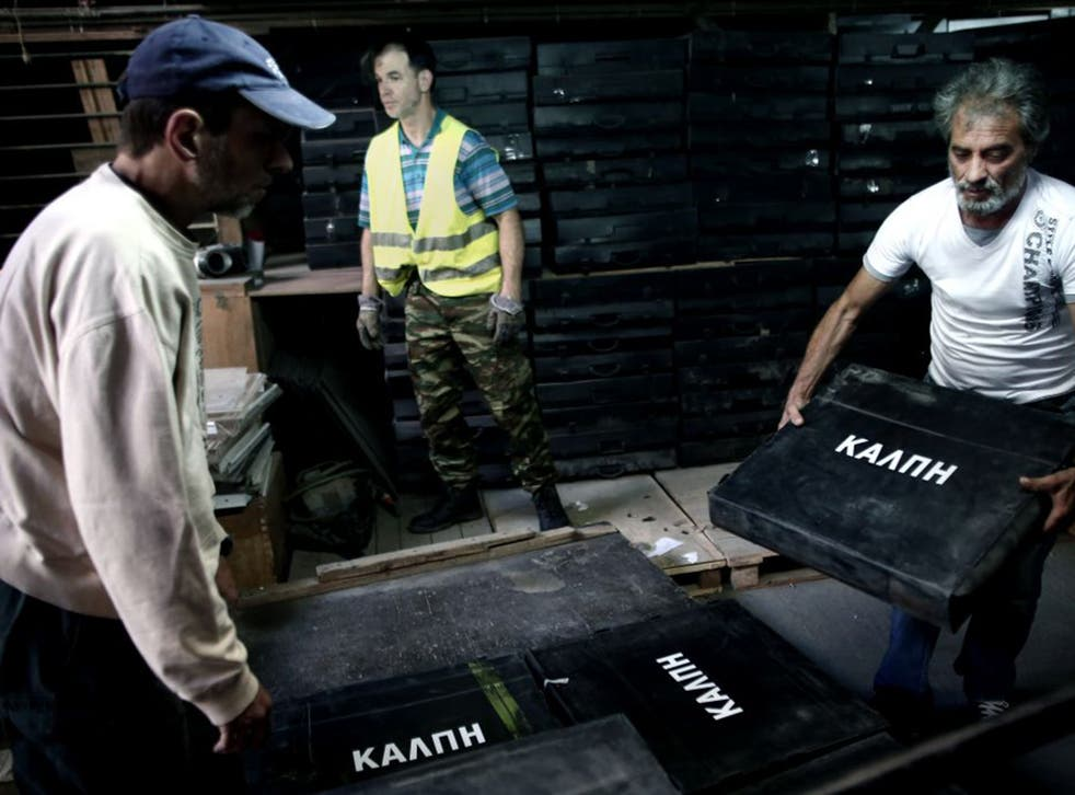 Municipal workers carry ballot boxes into a warehouse in Athens in preparation for the coming referendum