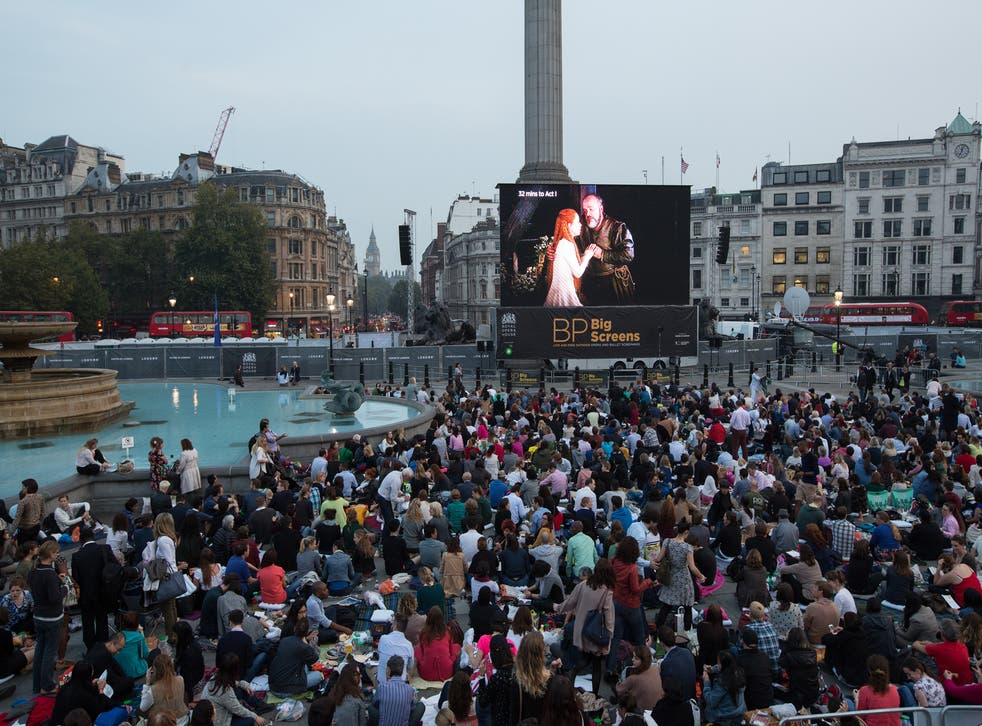 Members of the public prepare to watch a performance of Verdi's opera 'Rigoletto' on a big screen in Trafalgar Square displaying a live relay from The Royal Opera House on September 17, 2014
