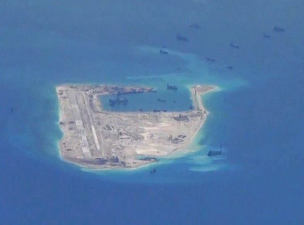 Chinese dredging vessels are purportedly seen in the waters around Fiery Cross Reef in the disputed Spratly Islands in the South China Sea in this still file image from video taken by a P-8A Poseidon surveillance aircraft provided by the United States Nav