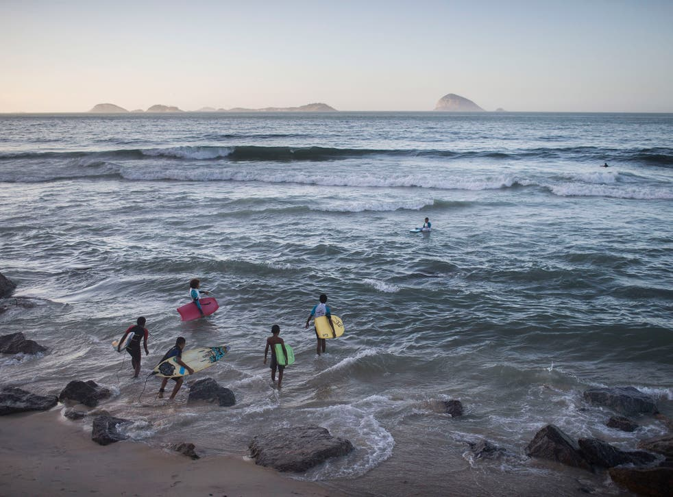 Young surfers from the Rocinha slum enter the water at Sao Conrado beach in Rio de Janeiro, Brazil. Everyday barefoot boys hustle down the inclined alleyways of the Rio de Janeiro slums they call home, surf boards under their arms. They head to nearby Sao
